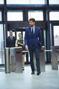 Businessman passing through turnstile gate Royalty Free Stock Photo