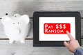 Businessman paying a ransom to ransomware on tablet device with piggy bank next to it Royalty Free Stock Photography