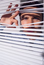 Businessman peeking through blinds close up portrait of a young Royalty Free Stock Photography
