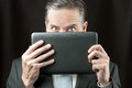 Businessman peeks over his tablet close up of a peeking Royalty Free Stock Photo