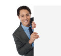 Businessman peeping from behind the blank board Stock Photo