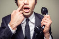 Businessman picking his nose young incompetent is on the phone and is Royalty Free Stock Image