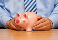 Businessman with piggy bank hands of at desk money box or savings concept Stock Photos