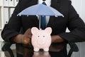 Businessman With Piggybank And Umbrella Royalty Free Stock Photo