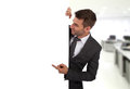 Businessman pointing at a blank board standing in an office Stock Photography