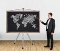 Businessman pointing at world map in tuxedo on blackboard Stock Images
