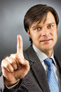 Businessman pressing an imaginary button against gray background Royalty Free Stock Images