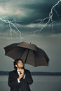 Businessman protecting himself from thunders the storm coming with an umbrella dark sky with Stock Photo
