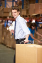 Businessman pulling pallet in warehouse smiling to camera Stock Photo