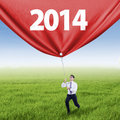 Businessman pulls banner on the meadow young is pulling big new year Royalty Free Stock Photos