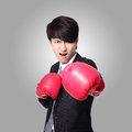 Businessman punching with boxing gloves Stock Photo