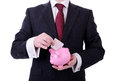 Businessman putting a euro note into a piggy bank concept of saving isolated on white Stock Photos