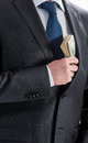 Businessman putting money in his pocket closeup shot Stock Photography