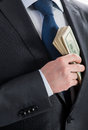 Businessman putting money in his pocket closeup shot Royalty Free Stock Images