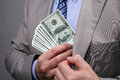 Businessman putting money in pocket man suit jacket concept for corruption bribing paying or business wealth Stock Photo