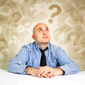 Businessman questioning thinking and loooking at question marks around his head Stock Photo