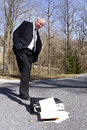 Businessman quitting kicking his fallen briefcase on the ground as in disgust or Royalty Free Stock Images