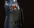Businessman reaching out leather briefcase Stock Photos