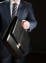 Businessman reaching out leather briefcase on black background Stock Images