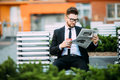 Handsome businessman reading a financial newspaper while sitting on bench outdoors Royalty Free Stock Photo