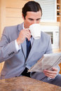 Businessman reading news and having a coffee Royalty Free Stock Image