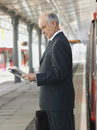 Businessman reading newspaper at empty train station side view of a mature an Stock Photography