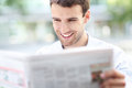 Businessman reading newspaper portrait of young business man smiling Stock Photo