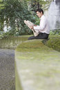 Businessman reading newspaper on wall in park side view of young Royalty Free Stock Photo