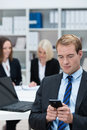 Businessman reading a text message on his mobile phone while sitting in busy corporate office Stock Photos