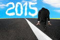 Businessman ready to run on asphalt road with 2015 cloud Royalty Free Stock Photo