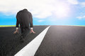 Businessman ready to run on asphalt road with sky sunlight Royalty Free Stock Photo