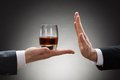 Businessman rejecting whisky offered by businessperson close up of hand reject a glass of Royalty Free Stock Images