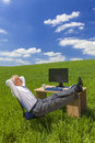 Businessman relaxing feet up desk in green field man or male at a with a computer a drinking tea or coffee Stock Photo