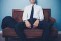 Businessman relaxing after long day at work is on an old vintage sofa a hard s in the office Royalty Free Stock Photos