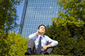 Businessman relaxing in park during lunch break Stock Photos