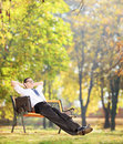 Businessman relaxing in park, seated on a wooden bench Royalty Free Stock Image