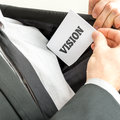Businessman removing or placing a card with word vision white in the inner pocket of his suit jacket Royalty Free Stock Images