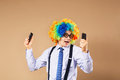Businessman respond to numerous phone calls businessman holding two mobile phones close up portrait of business man in clown wig Stock Photos