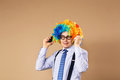 Businessman respond to numerous phone calls holding two mobile phones close up portrait of business man in clown wig Royalty Free Stock Image