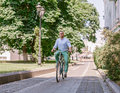 Businessman riding bicycle to work on urban street in morning. Royalty Free Stock Photo