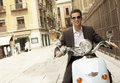 Businessman riding scooter through town portrait of handsome young Royalty Free Stock Image