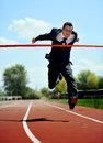 Businessman running on athletic track celebrating victory in work success concept Royalty Free Stock Photo