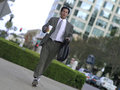 Businessman in running shoes with bag and coffee tilt Royalty Free Stock Photography