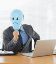 Businessman with sad smiley faced balloon at office desk Stock Photo