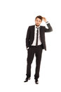 Businessman scratching his head in doubt stylish handsome young standing as he struggles to come to a decision full length Stock Images