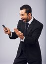 Businessman screaming in excitement while reading sms ecstatic from his cell phone Stock Image