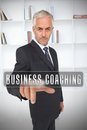 Businessman selecting the term business coaching in front of a bookcase Stock Photography