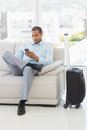 Businessman sending a text sitting on sofa waiting to depart on business trip in the office Stock Photography