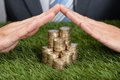 Businessman shielding stacked coins on grass cropped image of Stock Photo