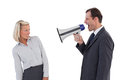 Businessman shouting at colleague with his megaphone on white background Royalty Free Stock Photography